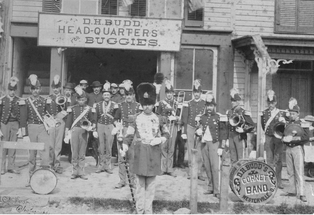 D.H. Budd's Cornet Band (Bands and Buggies) – David H. Budd had many interests including buggies (transportation) and music. This was one of the bands in the late 1800s that would play at fairs, parades and special events. This location later became the site of Schneider's Bakery.